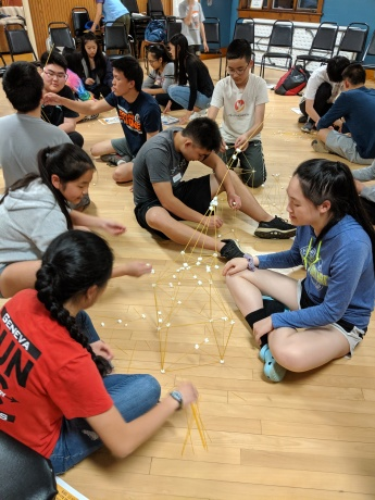 Building a tower using spaghetti sticks and marshmallows.